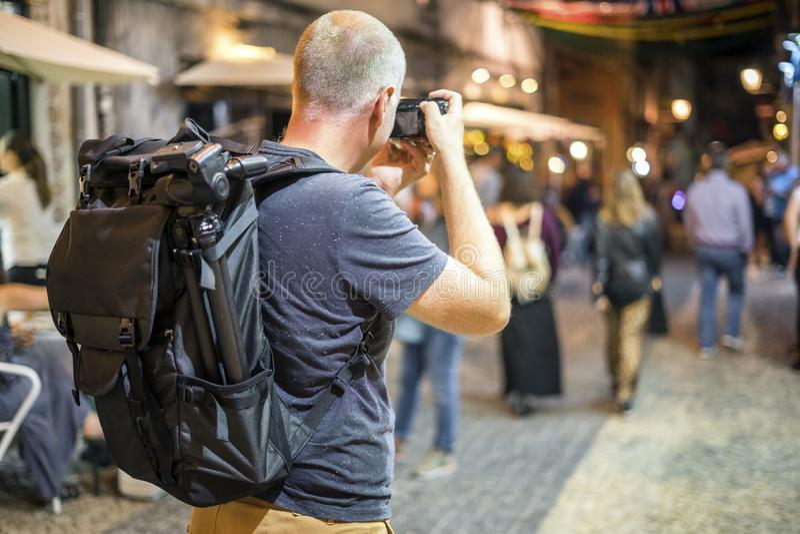 Fotograf som tar foto av livliga gator med restauranger royaltyfria bilder