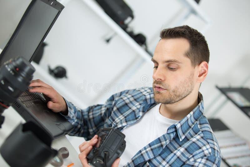 Fotograf sprawdza fotografie w kamerze przy biurkiem w biurze obraz stock
