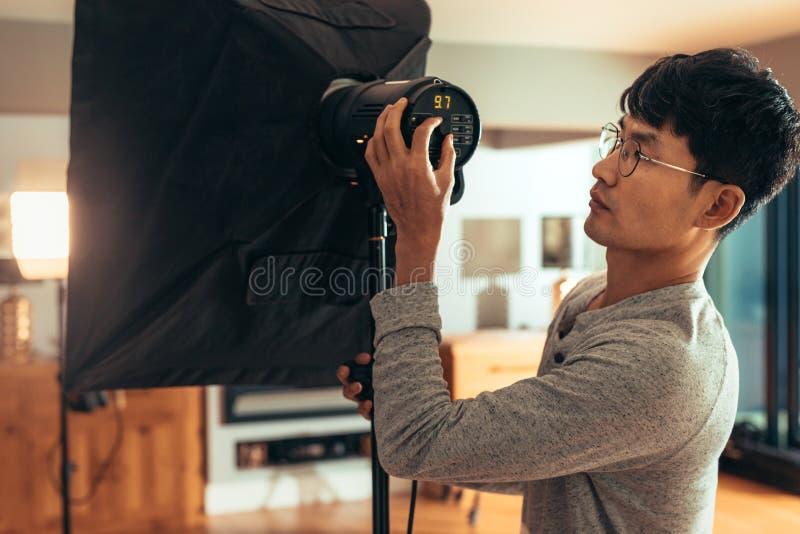 Fotograf stellen softbox Lichtstärke auf Trieb ein stockfotografie