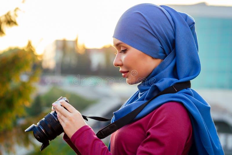Fotograf w hidżabie kobieta trzymająca hobbystę kamery lub dziennikarkę w jesiennych drzewach parku letniego fotografia stock