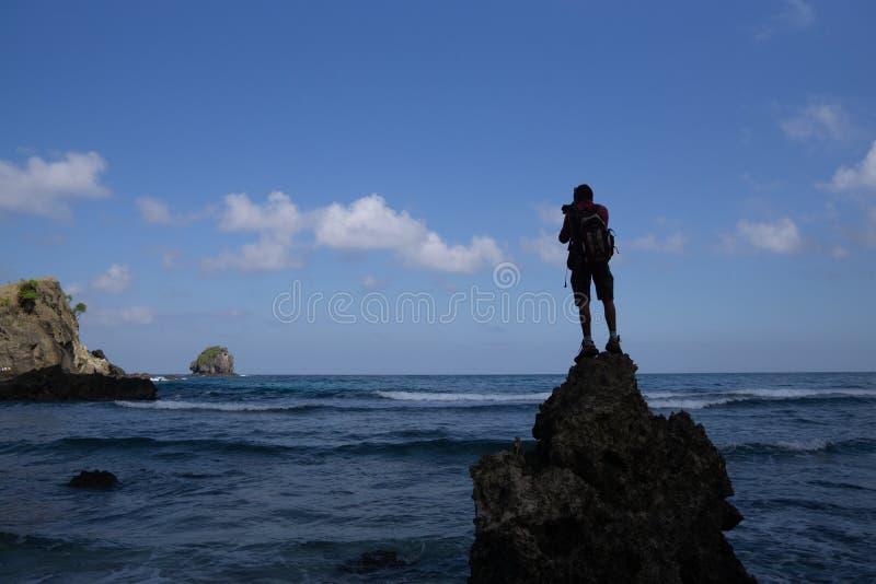 Fotograf wspinał się na skałach na plaży chwytać fotografie Koka& x27; s plaży krajobraz, Flores, Indonezja obrazy royalty free