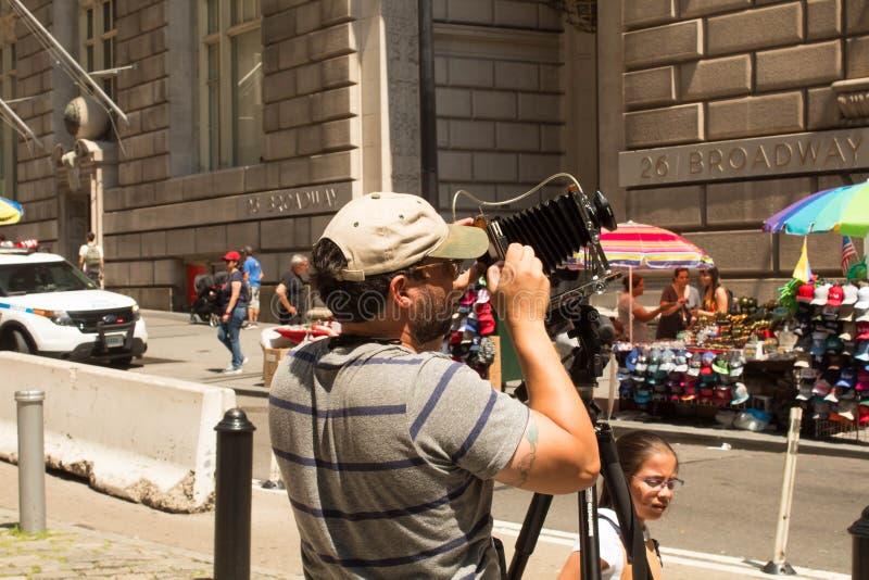 Fotograf z starą rocznika falcowania kamerą, Miasto Nowy Jork, NY, usa 08/04/2018 fotografia stock