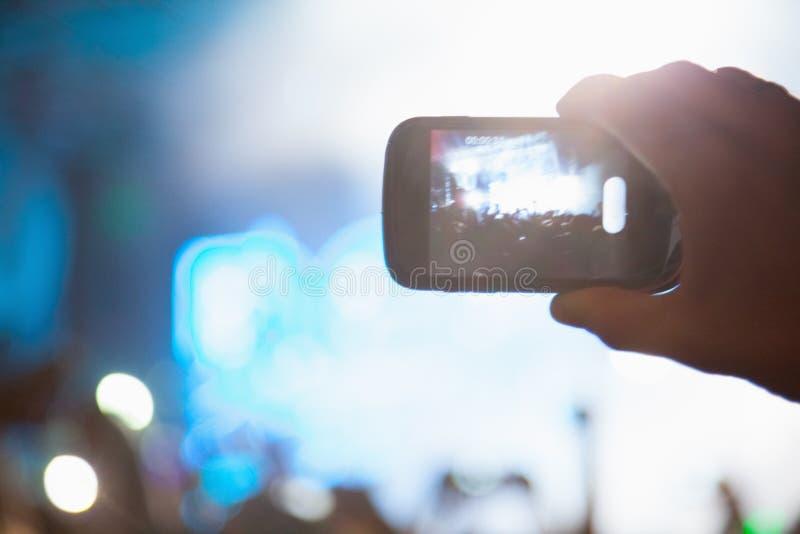 Fotografando con il telefono cellulare al concerto fotografia stock libera da diritti
