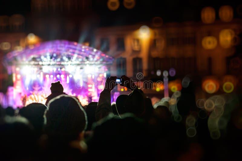 Fotografando con lo smartphone durante il concerto pubblico fotografia stock