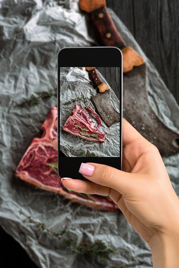 Fotografando concetto dell'alimento - la donna prende l'immagine di crudo asciuga le bistecche di bistecca con l'osso invecchiate immagine stock libera da diritti
