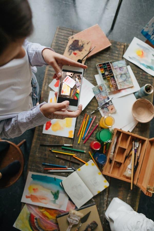Fotografando o processo de tirar imagens na aquarela Telefone celular da terra arrendada da moça do artista e fotos da tomada imagens de stock