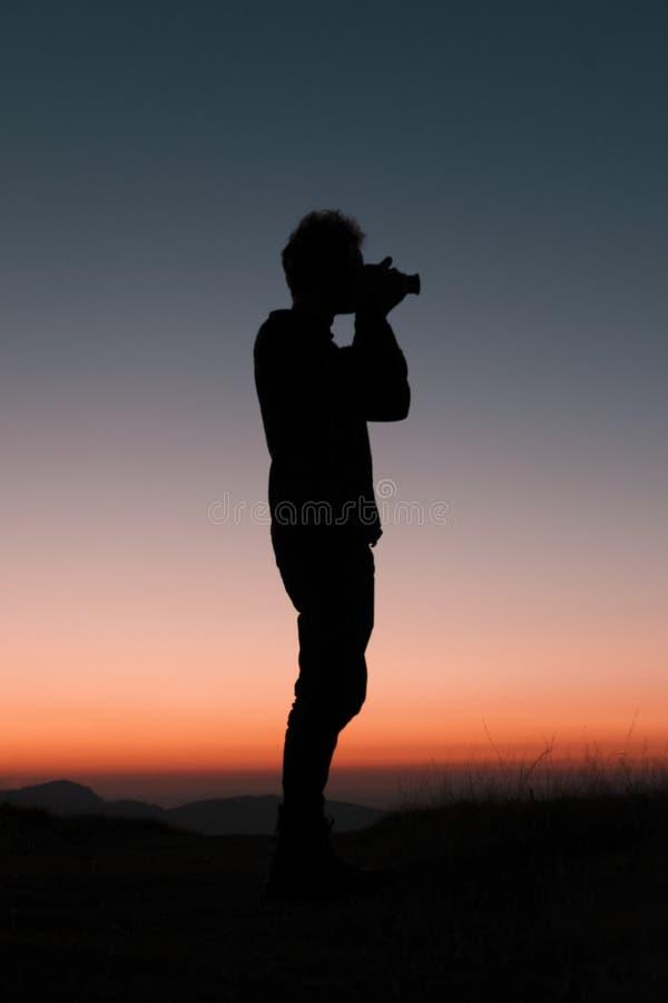 Fotografanseende med hans kamera i en härlig solnedgång som fångar detta ögonblick arkivfoto
