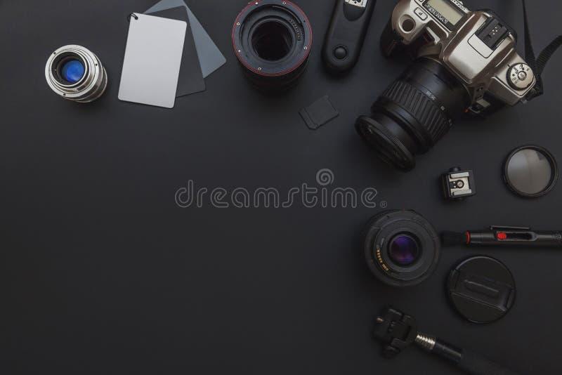 Fotografarbeitsplatz mit dslr Kamerasystem, Kamerareinigungsausrüstung, Linse und Kamerazubehör auf dunklem schwarzem Tabellenhin lizenzfreie stockfotografie