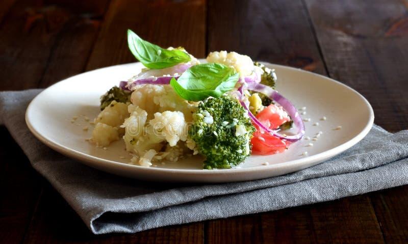 Fotografeerde de vitamine plantaardige salade van tomaten, broccoli, bloemkool, zoete uien, Basilicum en sesam close-up op bruine royalty-vrije stock foto
