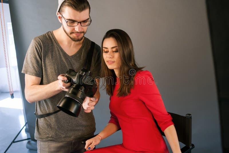 Fotografen meddelar med modellen på photoshoot royaltyfri foto