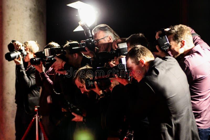 Fotografer som tar bilder på röd matta arkivbild