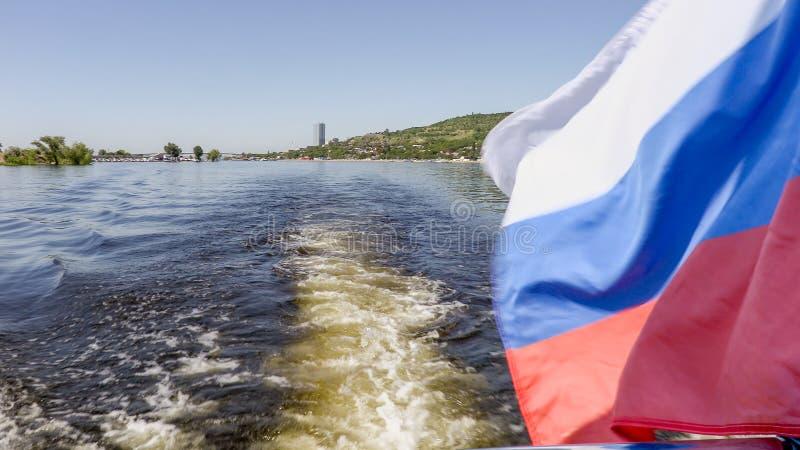 Fotografera från aktern av skeppet Sommarflodlandskap Volgaet River i Saratov, Ryssland Rysk flagga, det tricolor royaltyfri fotografi