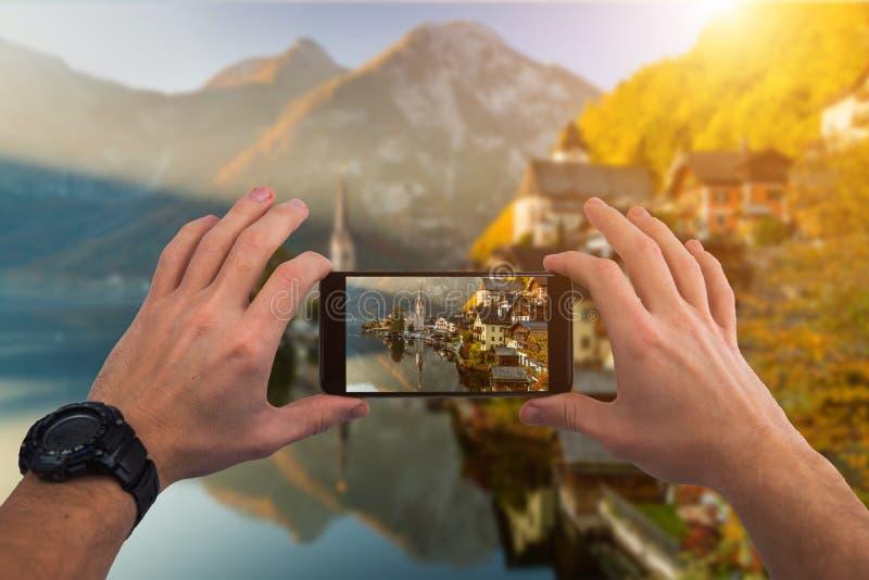 Fotografera med smartphonen i hand Hallstatt bergby, Österrike fotografering för bildbyråer