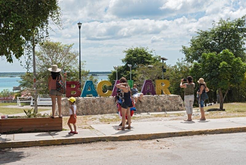 Fotografera turister framme av den bacalar kulöra bokstäver, Quintana Roo, Mexiko royaltyfri foto