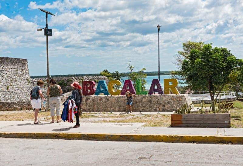 Fotografera turister framme av den bacalar kulöra bokstäver, Quintana Roo, Mexiko arkivbild