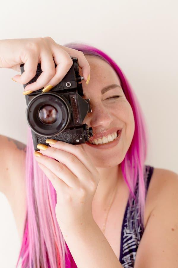 Fotografflicka med rosa hår på en fotofors med en kamera fotografering för bildbyråer