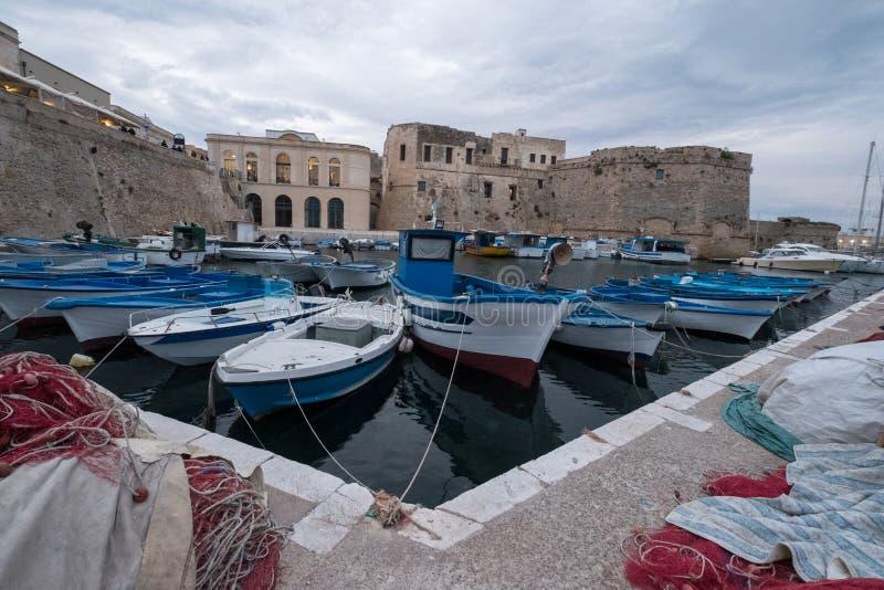 Fotografi av färgglade fiskebåtar i hamnen i staden av Gallipoli i den Salento halvön, Puglia, sydliga Italien fotografering för bildbyråer