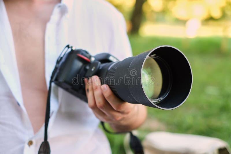 Fotografi eller handelsresandebegrepp Kameran för fotografhåll DSRL i hans händer med en stor lins på bakgrunden av naturen och s royaltyfri bild