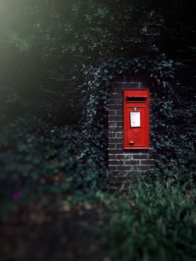 Fotografi för selektiv fokus av en röd postbox eller en brevlåda på en tegelstenvägg som omges av grönska arkivbilder