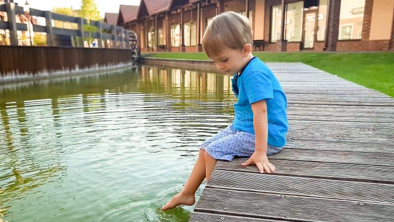 Fotografia śliczny 3 lat chłopiec obsiadanie na riverebank przy wodnym kanałem w starej miasteczka i chełbotania wodzie z ciekami zdjęcia stock