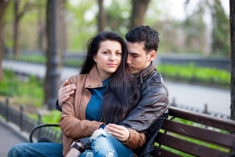 Fotografia śliczny pary obsiadanie na ławce i przytulenie na wygrywam zdjęcie stock