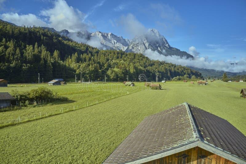 Fotografia aérea de baixa altura sobre o telhado de uma barraca de madeira sobre uma pastagem nos Alpes imagem de stock royalty free