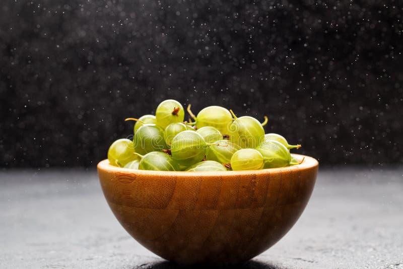 Fotografia agrestowe jagody w drewnianej filiżance i proszku pudrowaÅ' cukier zdjęcia royalty free