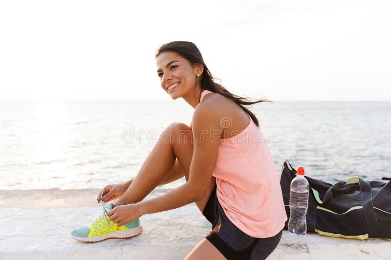 Fotografia atrakcyjna sporty kobieta 20s w tracksuit kucaniu, i zdjęcia stock