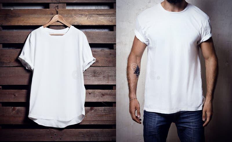 Fotografia biały tshirt obwieszenie na drewnianym tle i brodatym mężczyzna jest ubranym jasnego Tshirt Pionowo pusty mockup