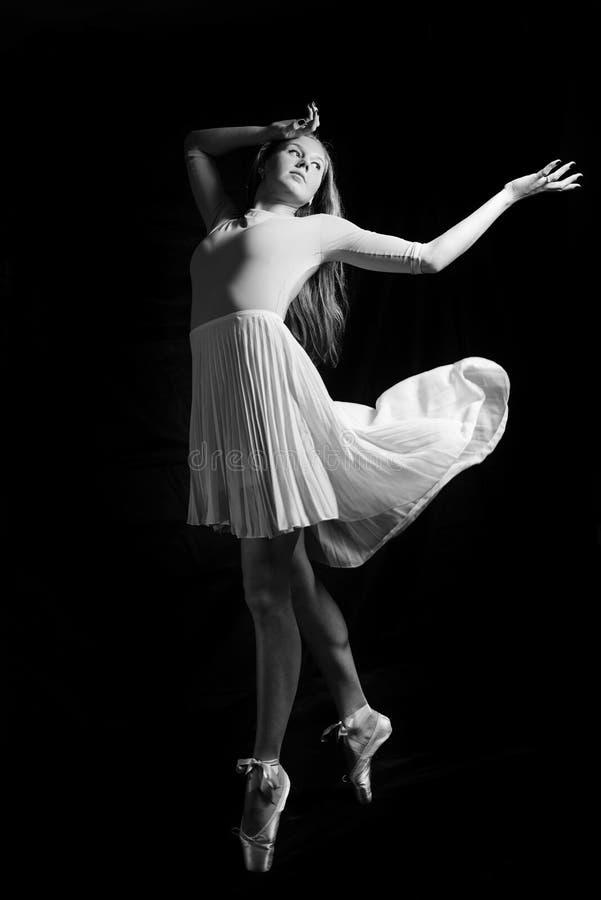 Fotografia in bianco e nero di bella giovane donna nel dancing sul copyspace scuro del fondo immagini stock