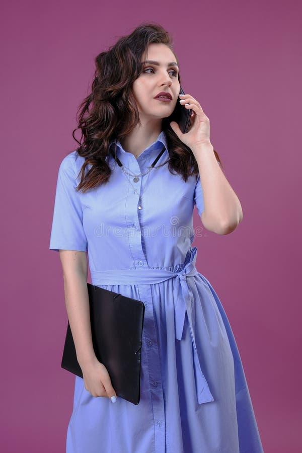 Fotografia biznesowa kobieta w błękit sukni mienia schowku z kartotekami i dzwonić z telefonem komórkowym nad różowym tłem obrazy stock