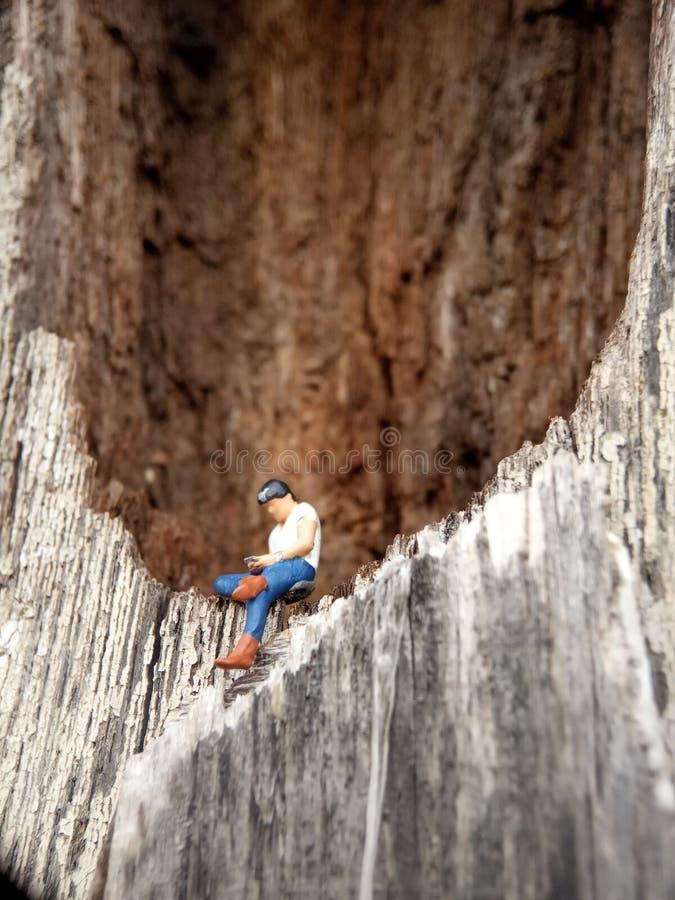 Fotografia Bliskiego Wschodu, Gadget Uzależniony Młody Człowiek, Holding Smartphone, siedzący w dziurze drewnianych drzwi obraz stock