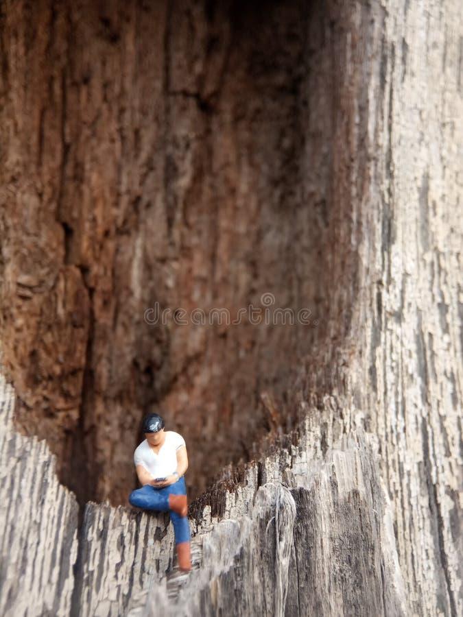 Fotografia Bliskiego Wschodu, Gadget uzależniony młody człowiek, trzymający smartfon, siedzący w dziurze Drzwi Wood obraz royalty free