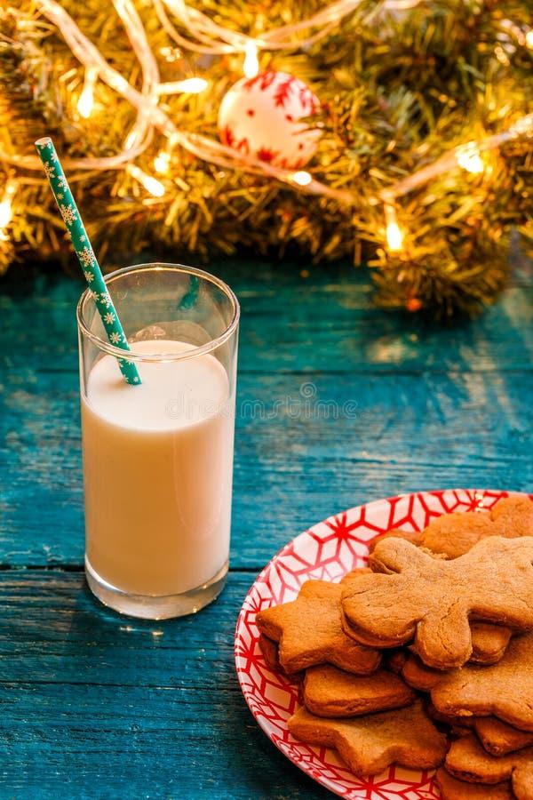 Fotografia Bożenarodzeniowi ciastka, szkło mleko, świerczyna rozgałęzia się z płonącą girlandą zdjęcia royalty free
