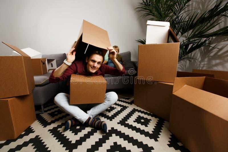 Fotografia brunet obsiadanie na podłodze wśród kartonów i śmiesznej kobiety z synem i córką obrazy stock