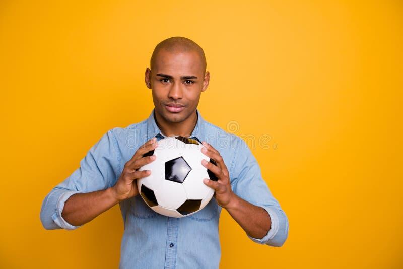 Fotografia ciemna skóra faceta chwyta ręk piłki poparcia faworyta drużyna chce sztuki odzieży cajgów drelichowa koszula odizolowy fotografia royalty free
