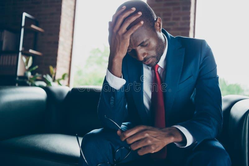 Fotografia ciemnego skóra faceta kanapy chwyta siedząca biurowa głowa na ręki odczucia oszołomionej odzieży eleganckim kostiumu fotografia stock