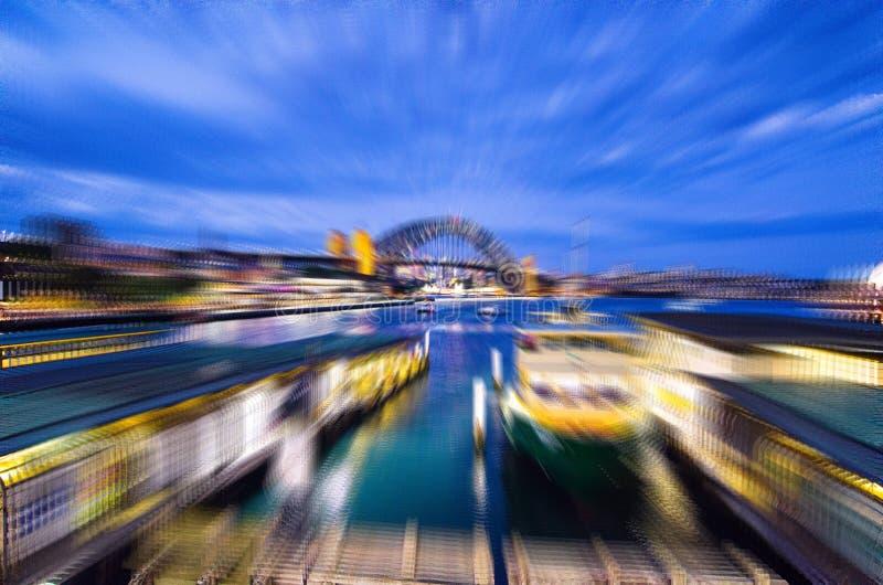 Fotografia da noite do borrão do zumbido do porto de Sydney com a ponte no centro da imagem, vista da estação de trem circular do fotos de stock royalty free
