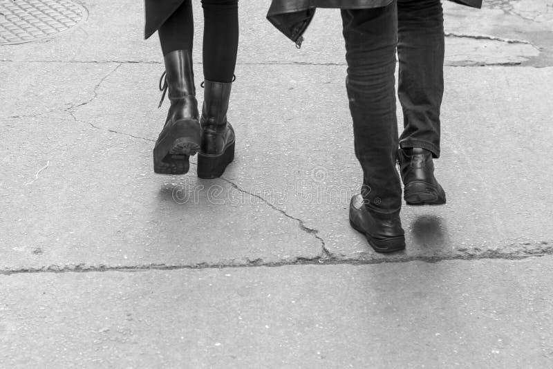 Fotografia da rua com o detalhe de um par gótico que anda com roupa preta foto de stock