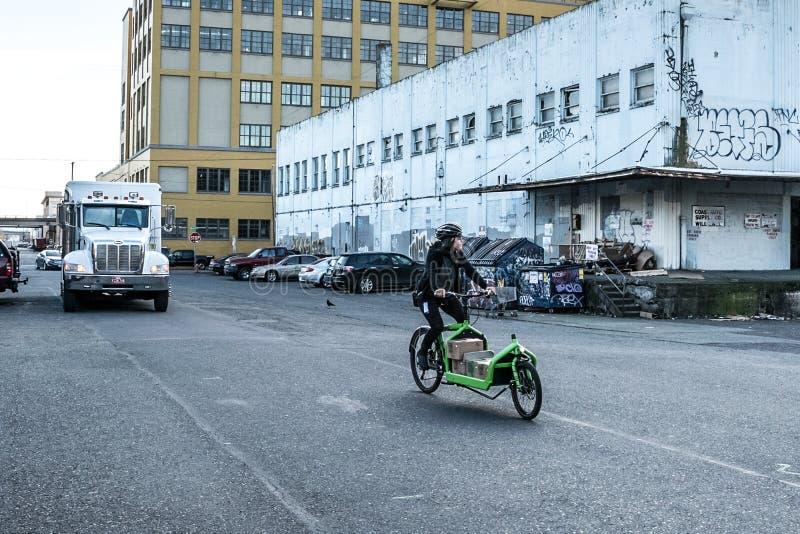 Fotografia da rua da mulher que monta sua bicicleta verde em Portland, Oregon Em dezembro de 2017 imagens de stock