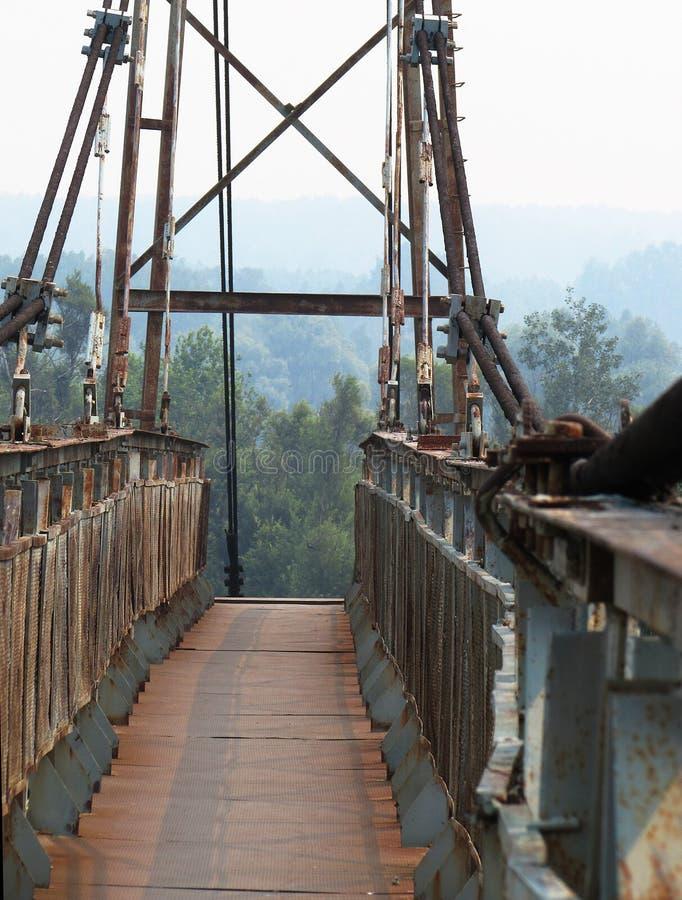 Fotografia de uma ponte pequena do ferro do metal com pranchas e os corrimão de madeira do metal imagens de stock royalty free