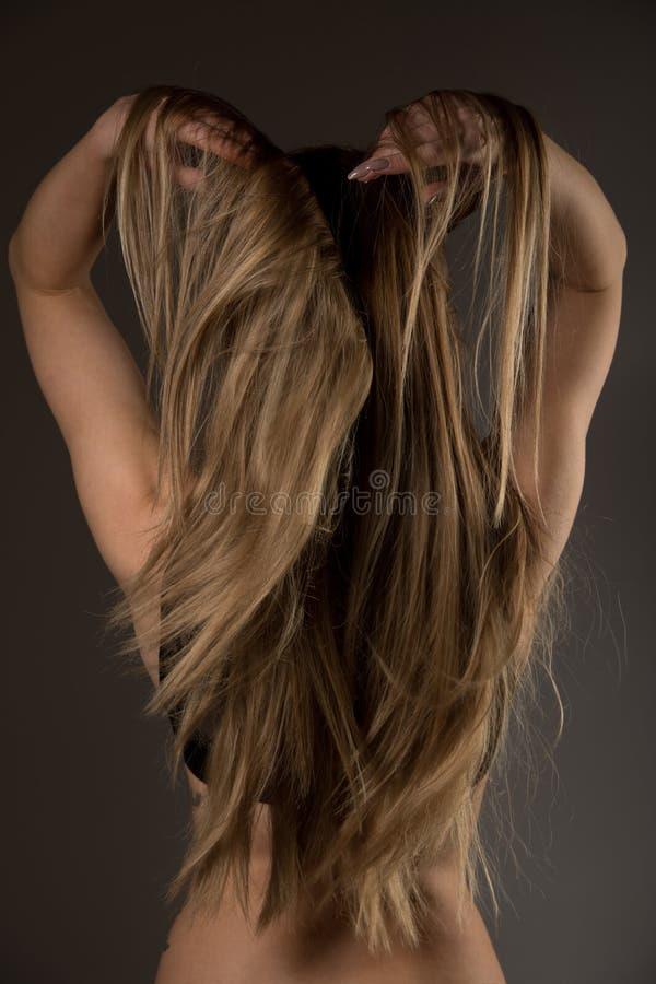 Fotografia del boudoir di bella giovane donna sopra il backgro scuro immagine stock