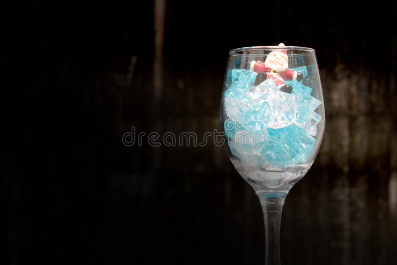 Fotografia di natura morta con Santa Claus in un bicchiere di vino con ghiaccio nella notte con fondo scuro, immagini stock libere da diritti