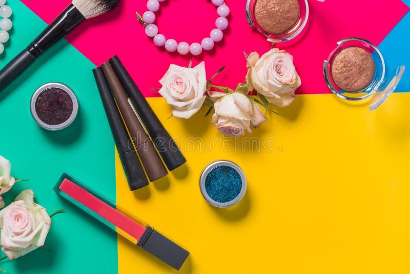 Fotografia di natura morta, cosmetici di a fondo luminoso colorato multi, rosa, giallo, verde, rossetto immagini stock libere da diritti