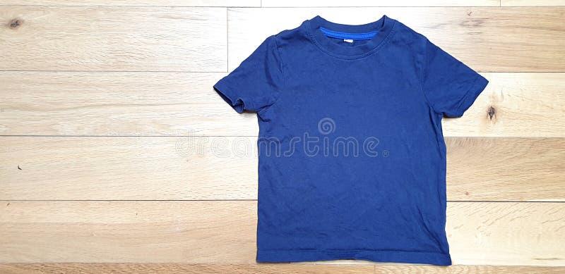 Fotografia di riserva disegnata, archivio Modello-digitale, derisione blu della maglietta del bambino su su fondo boscoso leggero fotografia stock libera da diritti