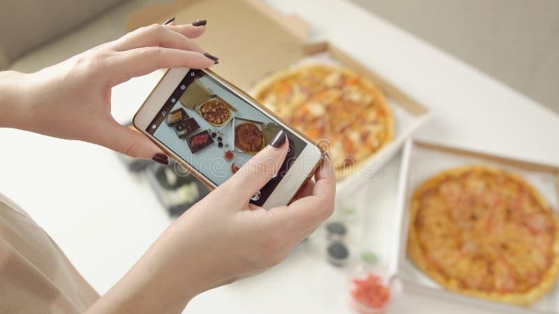 Fotografia do alimento As mãos tomam imagens da pizza e de rolos deliciosos com um smartphone imagens de stock