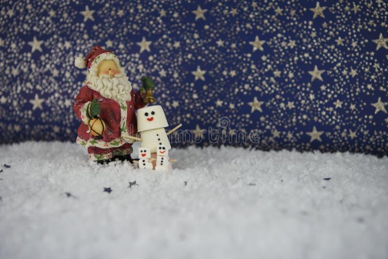 Fotografia do alimento do Natal dos marshmallows dados forma como o boneco de neve na neve com teste padrão de estrelas no fundo  foto de stock royalty free