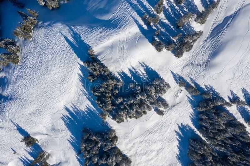 Fotografia do zangão da snowboarding e das trilhas do esqui deixadas na elevação da neve nas montanhas fotos de stock