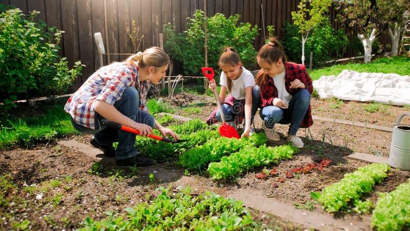 Fotografia dwa nastoletniej dziewczyny z macierzystym działaniem w podwórka ogródzie zdjęcia royalty free