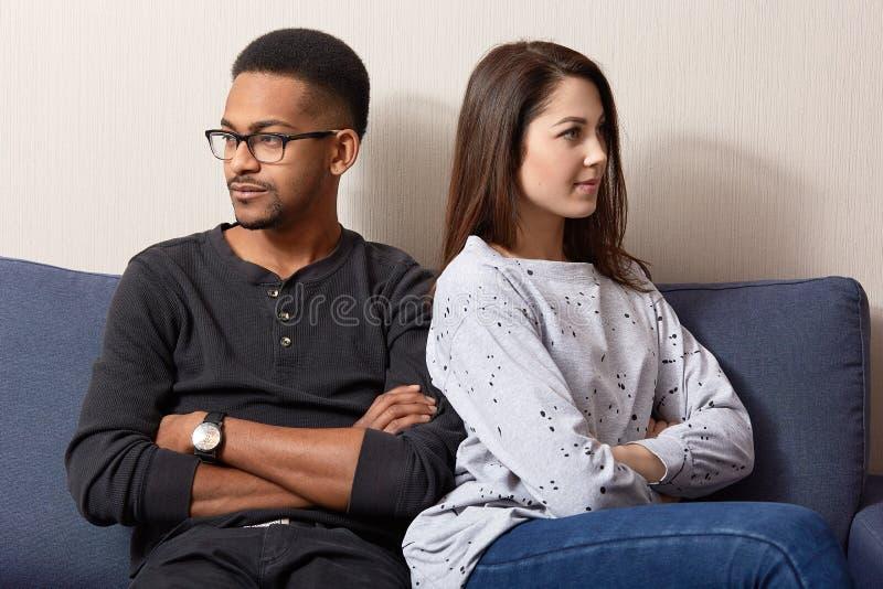 Fotografia dwa obrażającego młodzi ludzie w miłości odczuciu z zazdrością, zwrot od each inny, utrzymanie ręki krzyżować, kryzys  zdjęcia royalty free